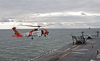 A U.S. Coast Guard helicopter preparing to land on the flight deck of the amphibious assault ship