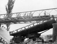 A Bailey bridge being deployed in the Korean War to replace a bridge destroyed in combat.