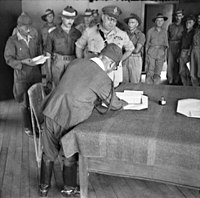 Major-General Wootten of the Australian 9th Division with Lieutenant-General Masao Baba (signing) of the Japanese 37th Division at the surrender ceremony at Labuan on 10 September 1945