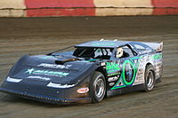 A late model car on a dirt track