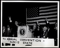 President Lyndon Johnson (left), alongside Illinois AFL-CIO President Reuben Soderstrom (center) and Vice President Stanley Johnson (right), speaks to the delegates of the 1964 Illinois AFL-CIO convention.