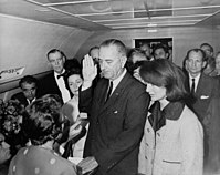 LBJ is sworn in on Air Force One by Judge Sarah Hughes as Mrs. Johnson and Mrs. Kennedy look on.