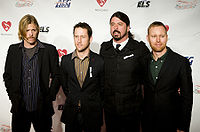 Foo Fighters in 2009; from left to right: Hawkins, Shiflett, Grohl, Mendel