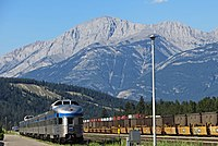 A Via Rail passenger train passing by freight trains in the background, at Jasper station