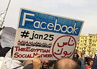 """A man during the 2011 Egyptian protests carrying a card saying """"Facebook,#jan25, The Egyptian Social Network"""""""