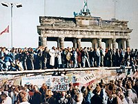 The Berlin Wall during its fall in 1989, with the Brandenburg Gate in the background
