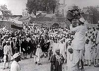 Hindus and Muslims, displaying the flags of both the Indian National Congress and the Muslim League, collecting clothes to be later burnt as a part of the non-cooperation movement initiated by Gandhi