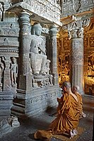 Buddhist monks praying in front of the Dagoba of Chaitya Cave 26 of the Ajanta Caves.