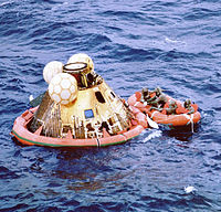 Columbia floats on the ocean as Navy divers assist in retrieving the astronauts