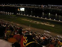 """Cars race by the """"DAYTONA"""" letters during the 2005 Pepsi 400."""