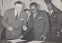 Maurice Yaméogo, the first President of Upper Volta, examines documents pertaining to the ratification of the country's independence in 1960