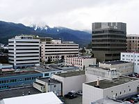 """The center of state government in Juneau. The large buildings in the background are, from left to right: the Court Plaza Building (known colloquially as the """"Spam Can""""), the State Office Building (behind), the Alaska Office Building, the John H. Dimond State Courthouse, and the Alaska State Capitol. Many of the smaller buildings in the foreground are also occupied by state government agencies."""