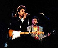 """Harrison and Eric Clapton performing """"While My Guitar Gently Weeps"""" at the 1987 Prince's Trust Concert in London"""
