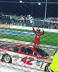 Larson waving the checkered flag in the air after winning the 2017 Federated Auto Parts 400 for his fourth win of the season and fifth win of his career