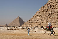 Tourists riding a Arabian camel in front of Pyramid of Khafre. The Giza Necropolis is one of Egypt's main tourist attractions.