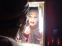 A drag queen preparing stage makeup