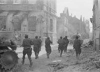 Soviet soldiers advance through the streets of Jelgava; summer 1944