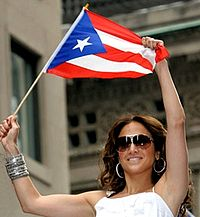 Lopez waving the Puerto Rican flag in 2009 at the Puerto Rican Day Parade in Manhattan