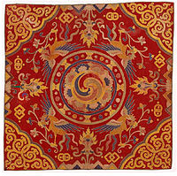 """A thrikhep (throne cover) from the 19th century. Throne covers were placed atop the temple cushions used by high lamas. The central circular swirling quadrune is the gankyil in its mode as the """"Four Joys""""."""