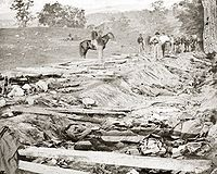 <center>Confederate dead at Bloody Lane, looking northeast from the south bank. Alexander Gardner photograph.<ref>The Union soldiers looking on were likely members of the 130th Pennsylvania, who were assigned burial detail</ref></center>