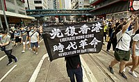 """On 1 July 2020, the day after implementation of the security law, tens of thousands of Hong Kong people gathered on the streets in Causeway Bay to march. On 2 July, the Hong Kong government declared the 'Liberate Hong Kong, revolution of our time' slogan depicted on a banner here – """"the most resonant slogan of its protest movement"""" – to be subversive and in violation of the law."""