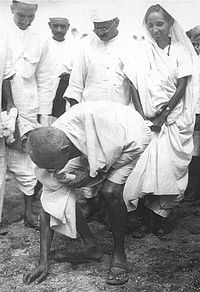 Gandhi picking salt during Salt Satyagraha to defy colonial law giving salt collection monopoly to the British. His satyagraha attracted vast numbers of Indian men and women.