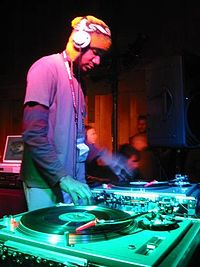A DJ mixing vinyl records with a DJ mixer at the Sundance Film Festival in 2003