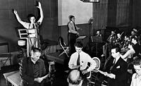 Herrmann conducts the CBS Radio orchestra at a rehearsal of The Mercury Theatre on the Air directed by Orson Welles (1938)