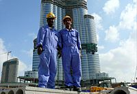 Two south Asian blue-collar workers posing for a picture with Burj Khalifa on the background.