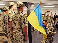 Henadii Lachkov, commander of the Ukrainian contingent in Multi-National Force – Iraq, kisses his country's flag