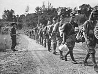 Disarmed Japanese troops marching towards a prisoner of war (POW) compound in Jesselton after surrendering to the Australian Imperial Force (AIF) on 8 October 1945.