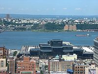 Hudson County and the Palisades, viewed across the Hudson River from Manhattan in the afternoon. The glass building visible is the Javits Center.