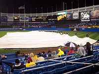 The grounds crew taking the tarp off the infield