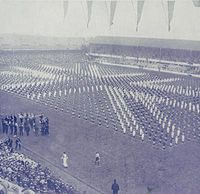 Men in dark blue and white suits stand across the pitch in formation, creating the image of a Union Flag. 80,000 people attended Goodison Park to see King George V.
