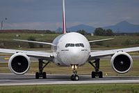 Front view of an Emirates 777-300ER, showing fuselage profile, wing dihedral, and GE90 engines