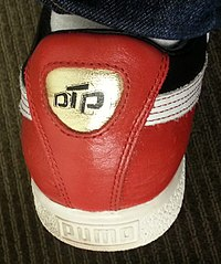Heel window of the Clyde x Luda Puma Clyde sneaker showing the Disturbing tha Peace logo