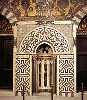 Mihrab of the mausoleum of Baybars, with marble mosaic paneling and glass mosaics above.