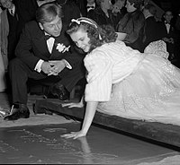 Mickey Rooney watching Garland put her handprint into concrete at Grauman's Chinese Theatre, 1939