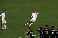 Beckham scoring with a bending free-kick in 2007. His typical pose when striking free-kicks or crossing the ball in open play, his body leans to the left to generate extra whip on the ball.