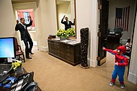 U.S. President Barack Obama pretending to be webbed up by a boy dressed in a Spider-Man costume inside the White House
