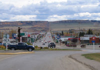 Looking south past traffic circle down 8 Street, with the metal statue pointing the way northwest to Alaska.