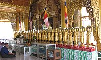 Buddhist men at the Sule Pagoda in Yangon, Myanmar, paying homage to the 29 Buddhas described in Chapter 27 of the Buddhavamsa