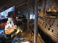 The main hall of the Vasa Museum with a scale model of Vasa as it might have looked on its maiden voyage to the left and the preserved ship itself to the right