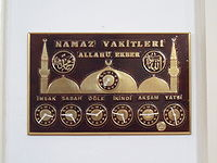 Display showing prayer times in a Turkish mosque.