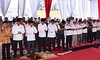 President Joko Widodo of Indonesia (front row, fourth from left) joining prayer in congregation with Vice President Jusuf Kalla (third from left), other cabinet members, and other worshippers.