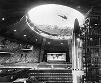 Blofeld's SPECTRE volcano base complete with spacecraft-swallowing Bird One spacecraft, helipad and attack helicopter, and command centre in the 1967 film You Only Live Twice. The world map in the background is common to emphasise the aim of world domination.