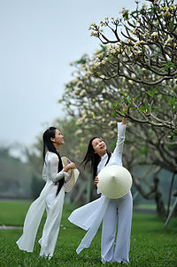 Vietnamese traditional white school uniform for girls in the country, the áo dài with the addition of nón lá, a conical hat.