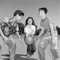 Lila Gee, playground monitor, with Chinese children playing basketball at McLean Park in Vancouver, 1951