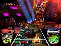 """Gameplay of a single player playing Pantera's """"Cowboys From Hell"""". The player in Guitar Hero must play the colored notes on the fret board in time with the music as they scroll through the target at the bottom. The score and current score multiplier are shown on the bottom left. The Rock Meter dial and Star Power indicator are shown on the bottom right. The remainder of the screen shows the player's character and band as they perform to the music."""